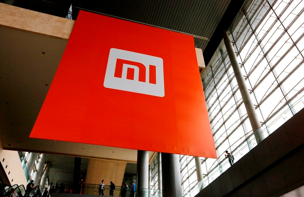 People stand near a logo of Xiaomi ahead of the launching ceremony of Xiaomi Phone 4, in Beijing, July 22, 2014. Picture taken July 22, 2014. REUTERS/Jason Lee (CHINA - Tags: BUSINESS TELECOMS LOGO) - RTR4857I