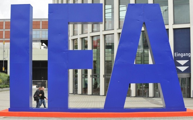 People walk past a giant IFA logo at the